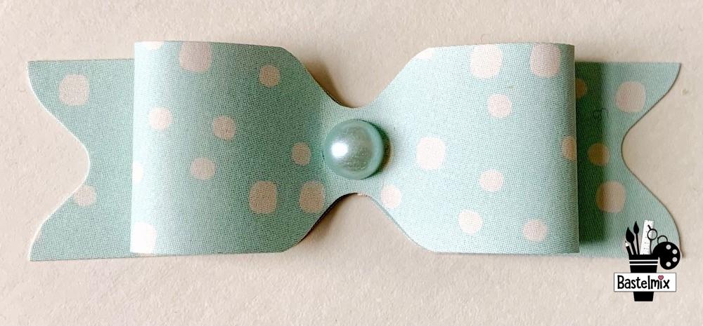 Papierschleife mit Perle in der Mitte.
